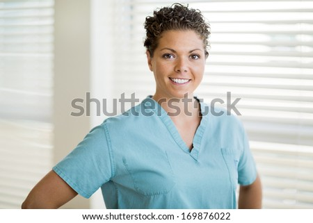 Portrait of happy female nurse in scrubs standing at clinic - stock photo