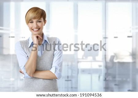 Portrait of happy female office worker at office. Space on right. - stock photo