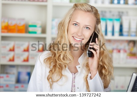 Portrait of happy female pharmacist communicating on cordless phone in pharmacy - stock photo