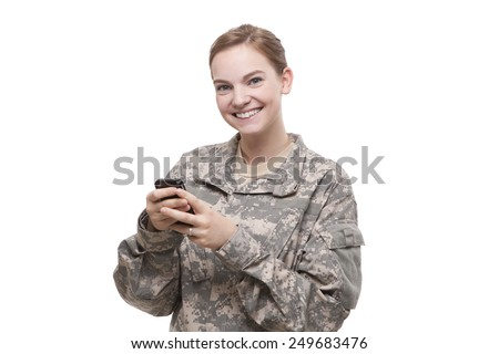 Portrait of happy female soldier text messaging against white background - stock photo