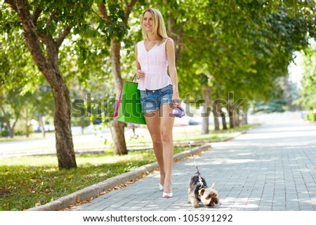 Portrait of happy female strolling with adorable pet in park - stock photo