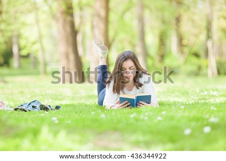 Portrait of happy female student reading a book on a sunny spring day. Young woman is lying on the grass in a park and smiling to camera. - stock photo