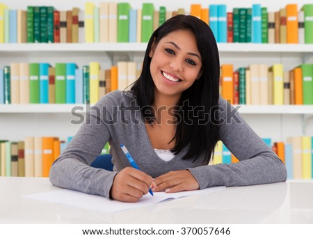Portrait of happy female student sitting at desk in library - stock photo