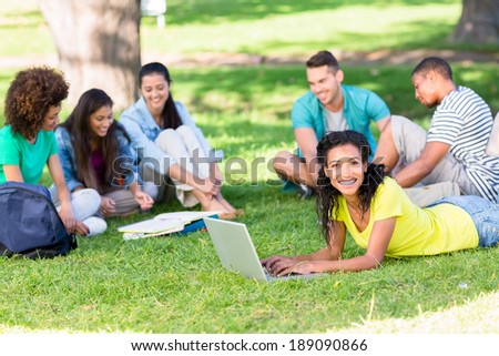 Portrait of happy female student using laptop on campus while friends studying in background