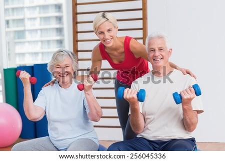 Portrait of happy female trainer with senior couple in fitness studio - stock photo