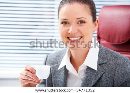 Portrait of happy female with cup of coffee looking at camera with smile - stock photo