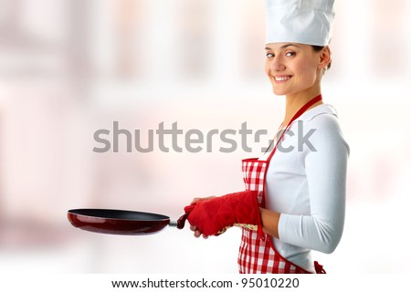 Portrait of happy female with frying pan looking at camera on creative background - stock photo