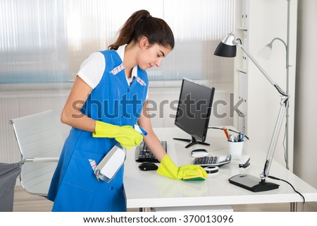Portrait of happy female worker cleaning computer desk with spray and sponge at office - stock photo