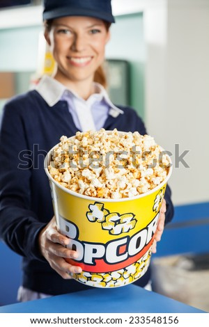 Portrait of happy female worker offering popcorn bucket at cinema concession stand - stock photo