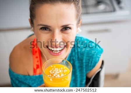Portrait of happy fitness young woman with pumpkin smoothie - stock photo
