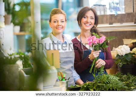 Portrait of happy florists making bouquet of pink roses in flower shop - stock photo
