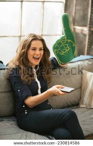 Portrait of happy football fan woman watching tv in loft apartment - stock photo