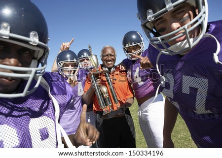 Portrait of happy football team and coach with trophy celebrating victory on field - stock photo