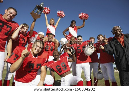 Portrait of happy football team with cheerleaders and coach celebrating success on field - stock photo