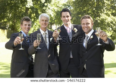 Portrait of happy four men toasting champagne flutes at wedding day - stock photo