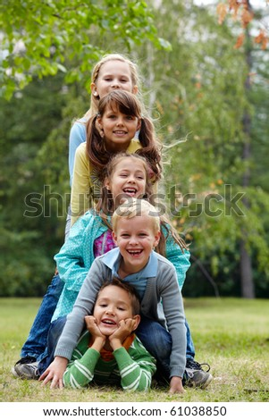 Portrait of happy friends lying on ground in park and looking at camera - stock photo