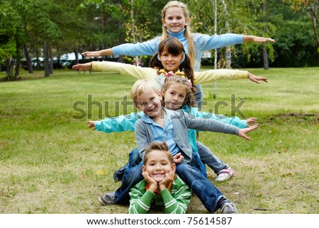Portrait of happy friends lying on ground in park with stretched arms - stock photo