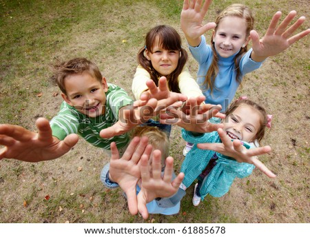 Portrait of happy friends standing on ground in park and stratching arms - stock photo