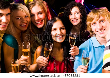 Portrait of happy friends with champagne looking at camera at birthday party