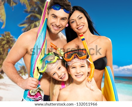 Portrait of  happy fun beautiful family with two children at tropical beach with protective swimming mask - stock photo