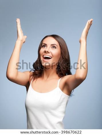 Portrait of happy gesturing or praying young beautiful woman looking up, in white casual clothing, over grey background - stock photo