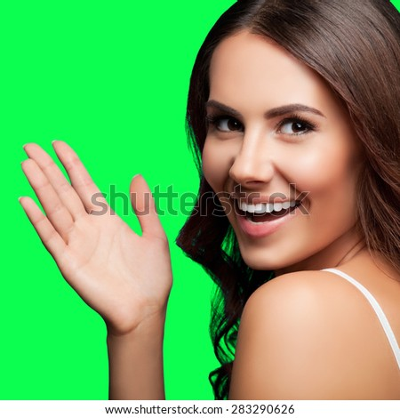 Portrait of happy gesturing smiling young beautiful woman, in white casual clothing, isolated over green screen chroma key background - stock photo