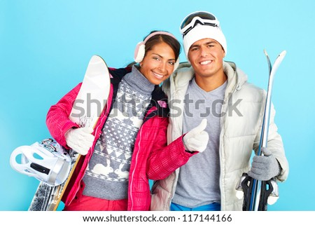 Portrait of happy girl and handsome man in winterwear holding snowboard ans skis
