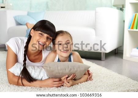 Portrait of happy girl and her mother looking at camera while resting at home