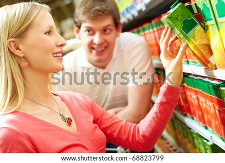 Portrait of happy girl choosing pack of juice in supermarket - stock photo