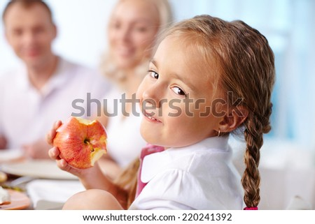 Portrait of happy girl eating apple and looking at camera on background of her parents - stock photo