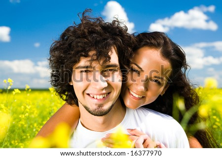 Portrait of happy girl embracing her boyfriend and both looking at camera with smiles in summer - stock photo