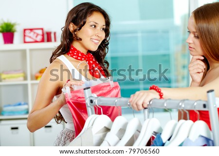 Portrait of happy girl giving advice to her friend of buying new dress in clothing department - stock photo
