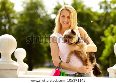Portrait of happy girl holding cute pet and looking at camera outside - stock photo