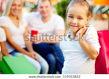 Portrait of happy girl holding paperbag and looking at camera in the mall with parents on background - stock photo