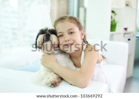 Portrait of happy girl holding shih-tzu dog and looking at camera - stock photo