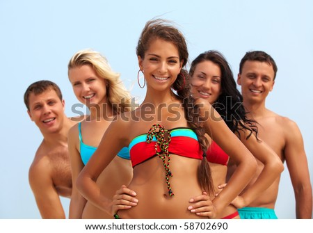 Portrait of happy girl in bikini looking at camera with friends behind