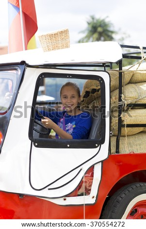 Portrait of Happy Girl in Old Car Having Fun Outdoors - stock photo