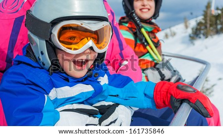 Portrait of happy girl in ski goggles and a helmet with his sister on the ski lift - stock photo