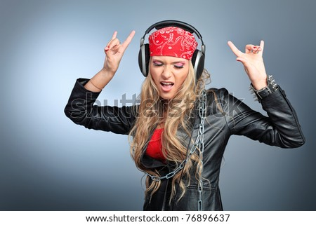 Portrait of happy girl listening a music in headphones. Studio shot over grey background. - stock photo