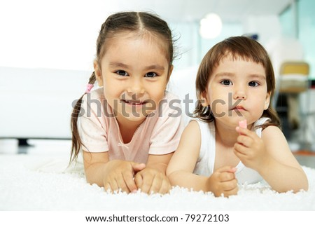 Portrait of happy girl looking at camera and smiling with her sister near by - stock photo