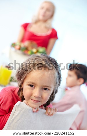 Portrait of happy girl looking at camera on background of her mother and brother - stock photo
