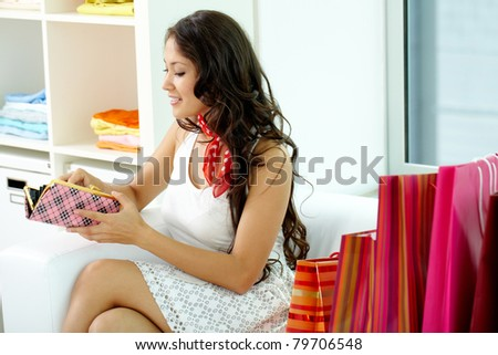 Portrait of happy girl looking into wallet with paper bags near by - stock photo