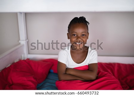 Portrait of happy girl sitting on bed at home