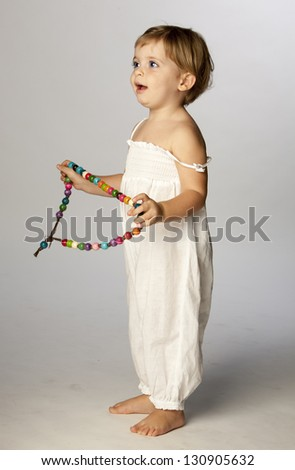 Portrait of happy girl with colorful necklace. - stock photo