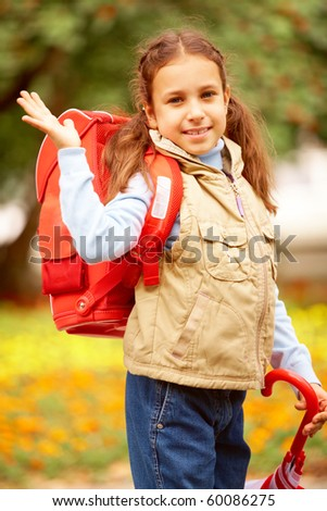 Portrait of happy girl with folded umbrella looking at camera on her way to school - stock photo