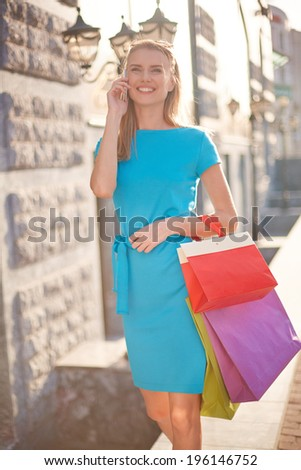 Portrait of happy girl with shopping bags calling outdoors - stock photo