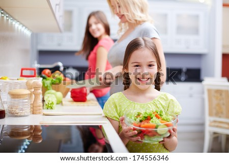 Portrait of happy girl with vegetable salad on background of her mother and sister cooking - stock photo