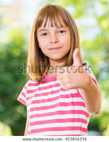 Portrait of happy girl 10-11 year old showing thumb up gesture. Beautiful schoolgirl posing outdoors. - stock photo