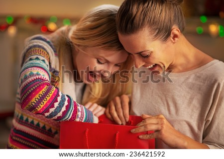 Portrait of happy girlfriends looking in shopping bag - stock photo