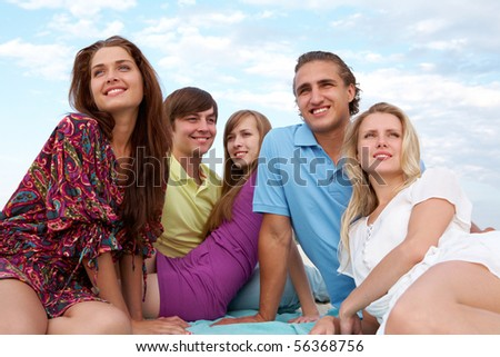 Portrait of happy girls and guys having rest outdoors